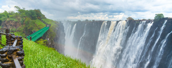 Walking way with view to the dramatic waterfall and clouds at Victoria Falls on the Zambezi River, Zimbabwe, Zambia.