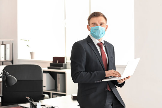 Male lawyer in protective mask working in office