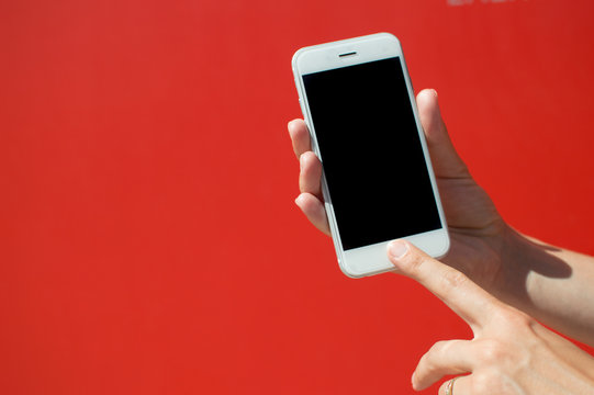 Close up on holding mobile smart phone over red background. Working remotely with information, modern communication lifestyle mock up display.