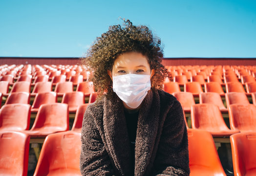Curly girl in a surgical mask sitting in an empty stadium during epidemic disease Covid-19.