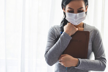 Portrait of a woman with a surgical mask on her face and a bible held tight to her chest