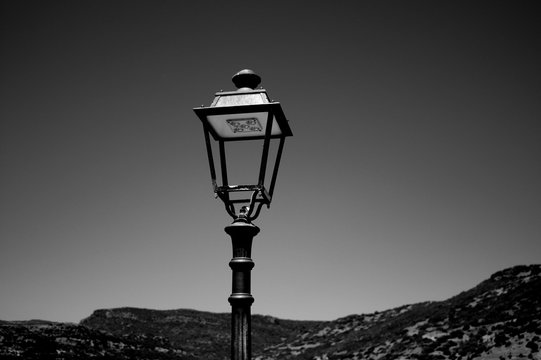 Old retro styled street lantern with electric lamp. Metal antique streetlight for urban illumination in vintage design.