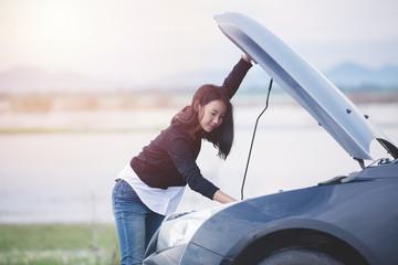 Asian woman checking broken down car on street