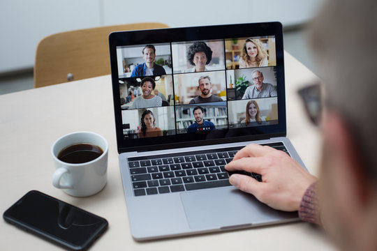 Person Using Video Conferencing technology in kitchen for video call with colleagues at home and in offices
