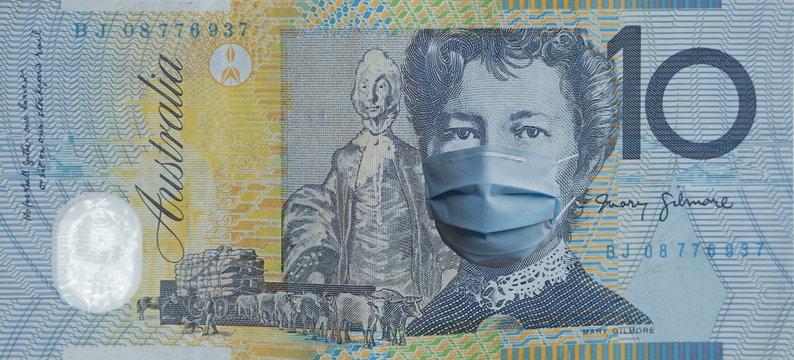 COVID-19 coronavirus in Australia, australian dollar money bill with face mask. COVID global stock market. World economy hit by corona virus outbreak. Financial crisis and coronavirus pandemic concept