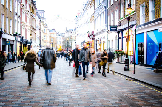 Motion blurred people on busy city street of shops