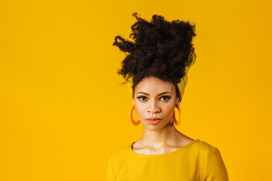 Portrait of a serious young woman with big yellow hoop earrings and hair wrapped with African head wrap scarf, isolated on yellow background