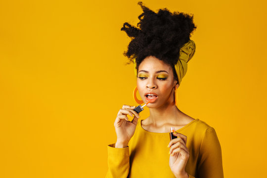 Portrait of a young woman with applying lipstick or lip gloss on lips, isolated on yellow background