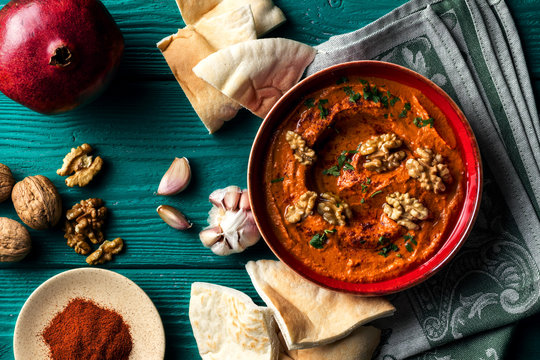 Roasted red bell pepper spread - muhammara - in a red bowl with various ingredients