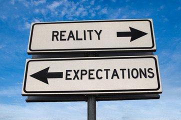 Reality vs expectation. White two street signs with arrow on metal pole with word. Directional road. Crossroads Road Sign, Two Arrow. Blue sky background. Two way road sign with text.