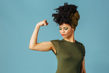 Portrait of a young woman showing her arm and strength and loking down