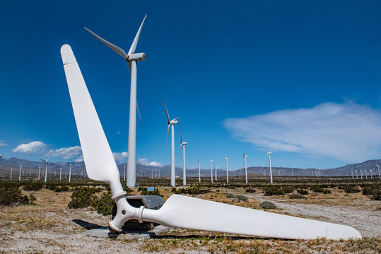 Old broken wind turbine blade in field of wind turbines