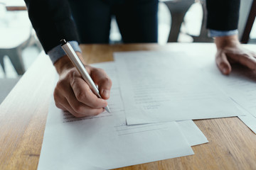 Close up hands signing documents in a modern office with window in background. Pen in hand, papers on the wooden desk, futuristic background.