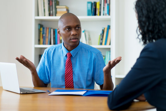 African american businessman talking to lazy employee