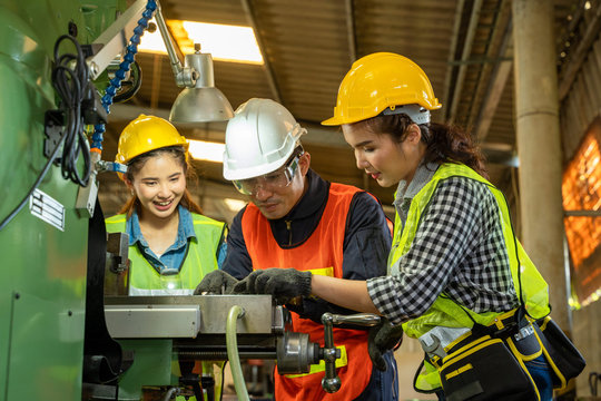 Engineers working in the factory,Team of workers and foreman checking machines in at factory.