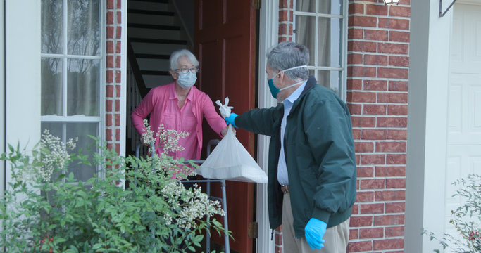 A senior citizen using a walker who is at high risk because of the coronavirus COVID19 gets meals or groceries delivered to her house by a volunteer working with a benevolent organization.