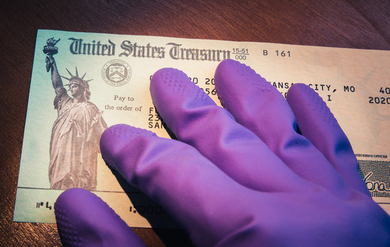 WASHINGTON DC - APRIL 5. 2020: United States Treasury check being held by rubber glove illustrates US Government coronavirus economic stimulus package as checks are sent to US taxpayers for relief.