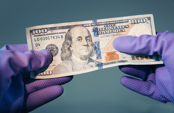 WASHINGTON DC - APRIL 5 2020:   $100 bill held by protective gloves. The Treasury Department and IRS have announced coronavirus stimulus checks as part of the government economic stimulus package.