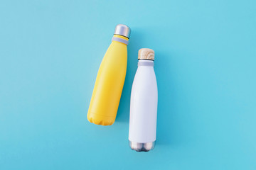 Reusable eco-friendly stainless steel thermo bottles on light blue background.