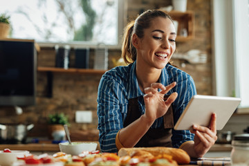 Young happy woman using digital tablet while preparing food in the kitchen.