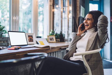 Caucasian female freelancer laughing while phoning during time for remote work on blank laptop with copy space area for internet advertising, cheerful woman talking via cellphone app and smiling Fotobehang