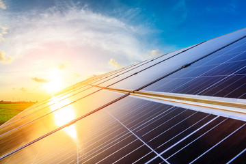 Photovoltaic solar panels on sunset sky background,green clean energy concept.