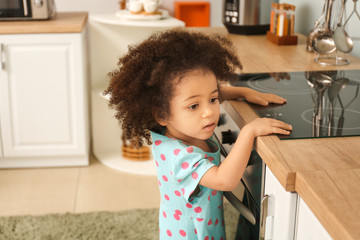 Little African-American girl playing with stove in kitchen. Child in danger Wall mural