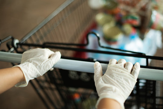 Woman wearing gloves to prevent coronavirus while using a shopping cart