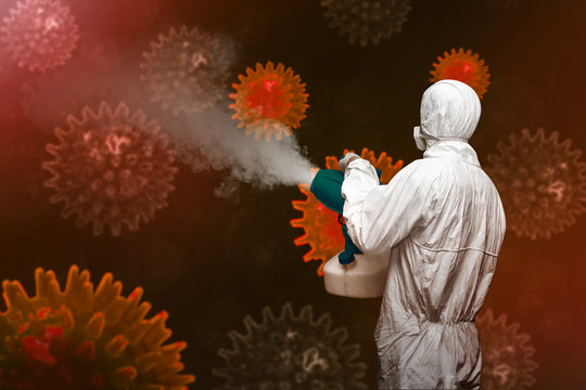 Man in a white protective suit spraying disinfectant