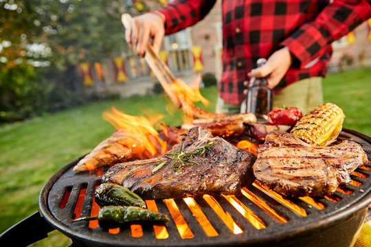 Man holding a beer grilling meat on a BBQ