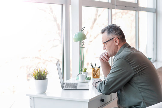 Mature man using laptop at home