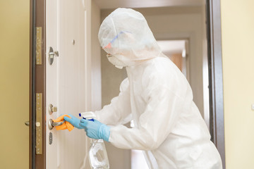 Woman worker disinfects door handles of house from infection with virus and microbes in biochemical suit. Coronavirus protection concept Wall mural