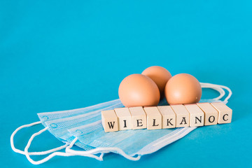 Eggs lying on face masks, wooden letters,