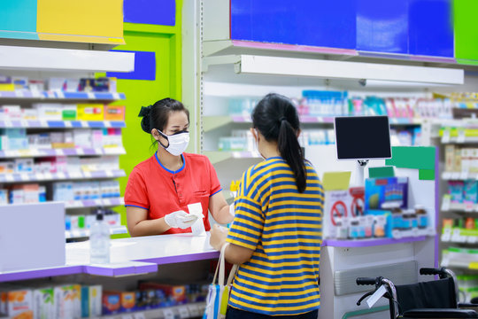 Pharmacist in medical face mask talking with a customer at the pharmacy desk