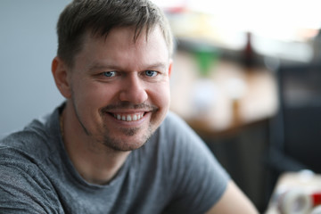 Close-up of smiling middle-aged man looking in camera. Cheerful attractive person dressed in grey shirt. Copy space in right side. Modeling and happiness concept Fototapete