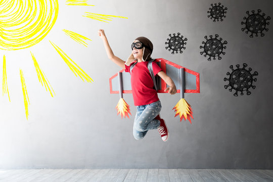 Happy child jumping with toy cardboard wings