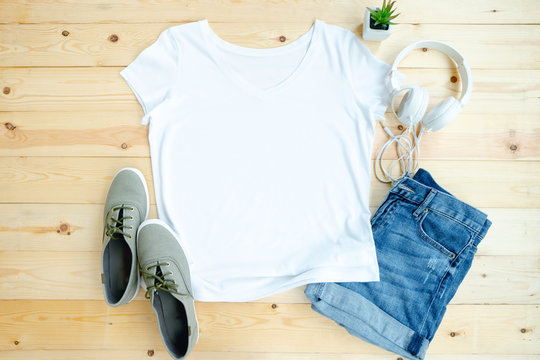 White female t shirt mock up flat lay on wooden background. Top front view
