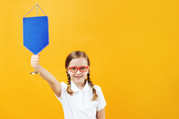 Portrait of a little schoolgirl girl in glasses on a yellow background. The child holds a pennant in his hands. The concept of education, success, achievement, discounts, sales. Copy space