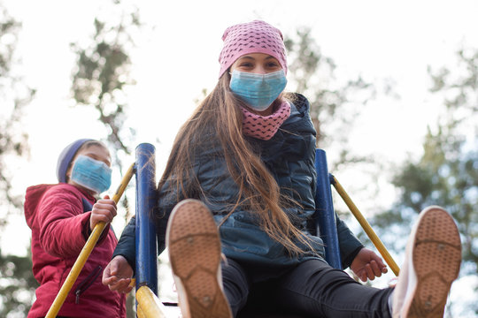Boy and girl having marry time on playground during coronavirus quarantine. Children don`t stay at home during dangerous epidemic