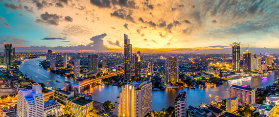 Poster Bangkok Aerial view Bangkok City skyline and skyscraper on Sathorn Road business and financial in Bangkok downtown, Panorama of Taksin Bridge over Chao Phraya River, Bangkok, Thailand at sunset.