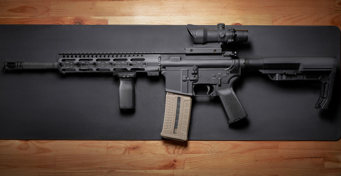 AR-15 rifle on wooden table.