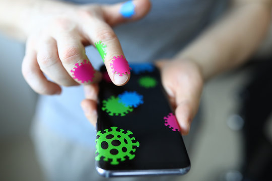 Close-up of persons hand holding mobile phone covered with microbe stickers. Bacteria on skin and personal stuff. Hygiene and health. Germs carrier concept