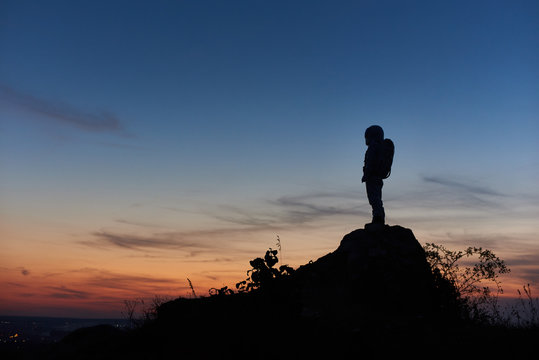 Silhouette of astronaut standing on top of rocky hill with beautiful night sky on background. Space traveler wearing space suit with helmet. Concept of space travel.