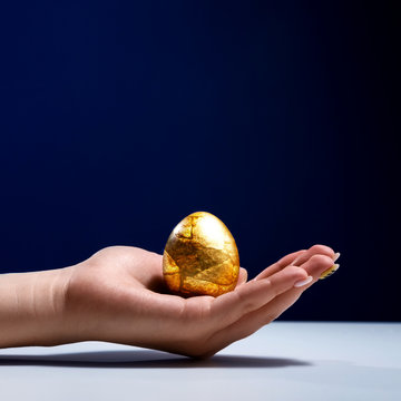 Female hand holding a Golden aaico. The egg in the rka is one. The egg has the texture of a stone. Ready-made solution for the designer. Easter concept. Meditation and spiritual development of the