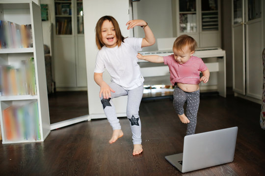 Funny children dance, do sports exercises online. Authentic lifestyle in a real interior