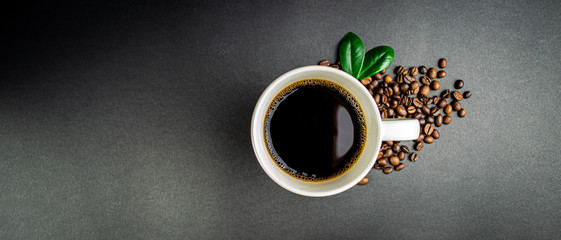 Photo sur Plexiglas Cafe Cup of coffee with roasted beans and green leaves on black background