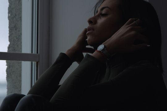 Depressed sad young african american woman feels anxiety stress sit alone by the window at home. upset worried mixed-race lady having psychological problem concept