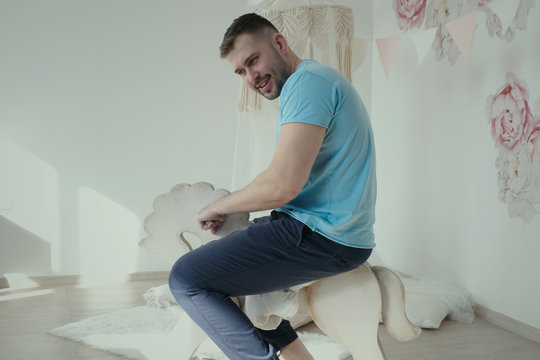 Adult autistic man riding a toy horse in child room, smiling man wearing casual clothes riding on toy wooden horse