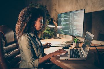 Profile side photo focused skilled afro american girl web designer geek freelancer entrepreneur sit evening table work computer laptop write binary java script code in workstation workplace