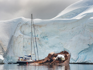 sail yacht and ship wreck under huge glacier in Antarctica